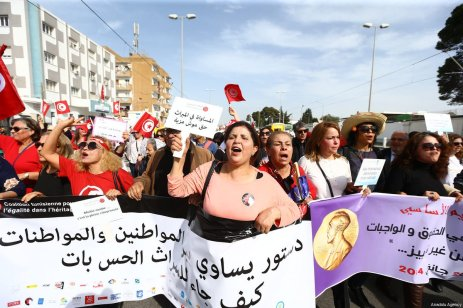 Hundreds of demonstrators hold placards and shout slogans during a march from Bab Sadun to Bardo square, demanding equal inheritance rights for women in Tunis, Tunisia on March 10, 2018 [Yassine Gaidi / Anadolu Agency]