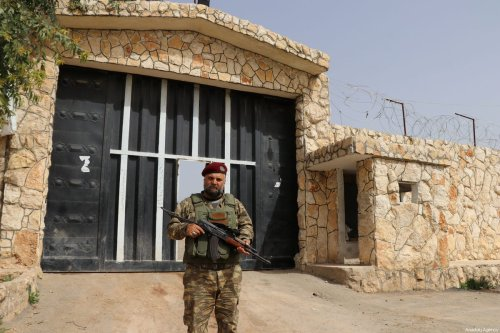 """A member of Free Syrian Army (FSA) poses for a photo in front of a prison, which was used by PKK to withhold opponents, after it was captured by FSA following the liberation of Afrin by Turkish Armed Forces and FSA within the """"Operation Olive Branch"""" launched in Syria's Afrin, on March 24, 2018 [Hişam El Homsi - Anadolu Agency]"""