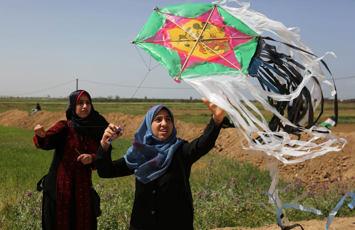 A Palestinian woman flys kite during a protest in a tent city along Israel border with Gaza, demanding to return to their home land, east of Gaza City, 29 March, 2018 [Ashraf Amra/Apaimages]