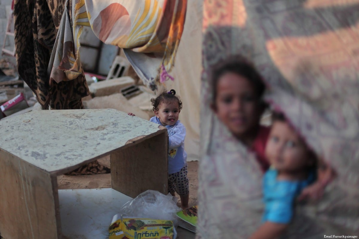 Palestinian children play outside their home in the poverty-stricken quarter of Al-Zaytoon in Gaza City on 29 September 2014 [Emad Nassar/Apaimages]