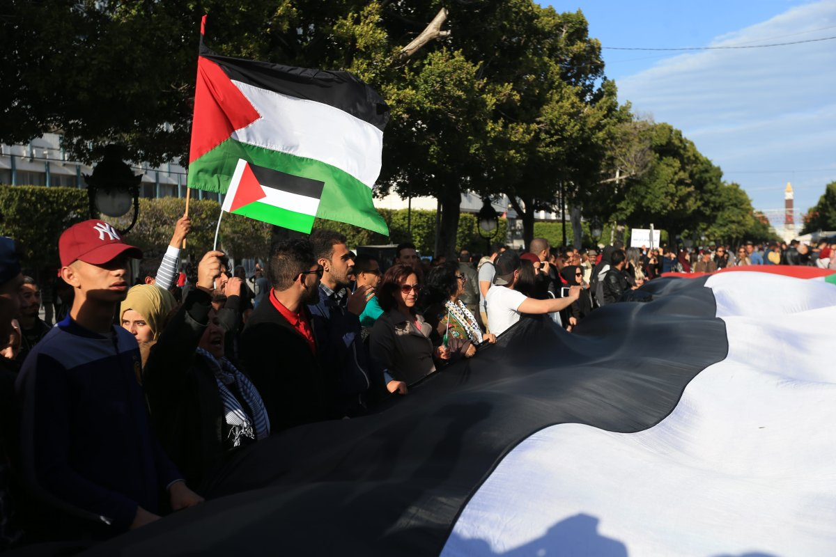 """People carry a massive Palestinian flag during a demonstration marking the 'Palestinian Land Day' at the Habib Bourguiba Avenue in Tunis, Tunisia on March 31, 2018. Land Day"""" is an annual Palestinian commemoration for the killing of six Palestinians by Israeli forces in 1976 [Yassine Gaidi / Anadolu Agency]"""