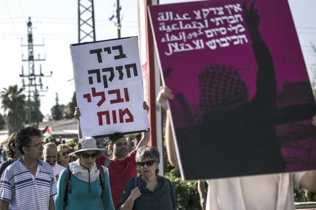 "Members of ""Coalition of Women for Peace"" consisting of Israeli and Palestinian activists hold banners during a protest held to support the ""Great March of Return"" near the Gaza border in Sderot, Israel on 31 March, 2018 [Stringer/Anadolu Agency]"