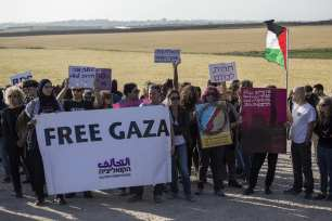 """Members of """"Coalition of Women for Peace"""" consisting Israeli and Palestinian activists hold banners during a protest held to support the """"Great March of Return"""" near the Gaza border in Sderot, Israel on 31 March, 2018 [Stringer/Anadolu Agency]"""