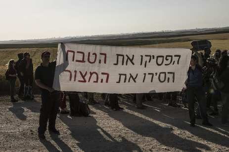 "Members of ""Coalition of Women for Peace"" consisting Israeli and Palestinian activists hold banner during a protest held to support the ""Great March of Return"" near the Gaza border in Sderot, Israel on 31 March, 2018. [Stringer/Anadolu Agency]"