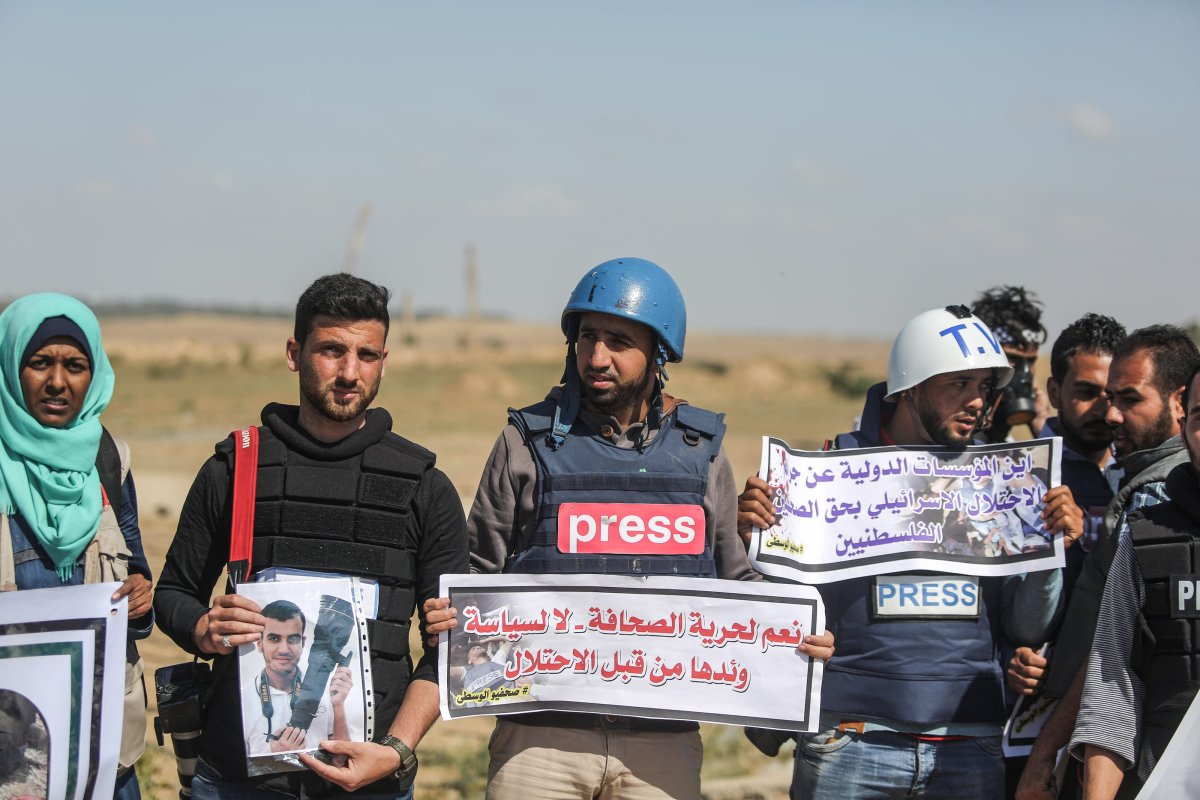 "Palestinian journalists hold placards to commemorate their Palestinian colleague Yasir Murteca, who was martyred by Israeli soldiers during ""Great March of Return"" near Gaza-Israel border, during a protest in Gaza City, Gaza on 9 April, 2018 [Ali Jadallah/Anadolu Agency]"
