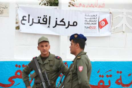 A banner is seen as Tunisian security officers stand guard at a polling station during Tunisian local elections, which was held first time after 2011 Arab Spring revolution, in Ben Arous, Tunisia on May 06, 2018. ( Yassine Gaidi - Anadolu Agency )