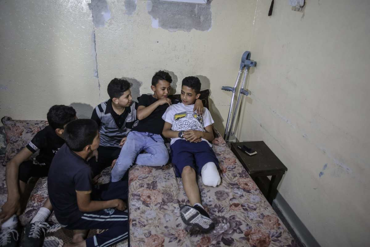 "11-year-old Gazaian Abdurrahman Nevfel (R), who lost his leg after Israeli soldiers opened fire on ""Great March of Returns"" demonstrations at Gaza Strip, is seen with his crutch in Gaza City, Gaza on 12 May, 2018 [Ali Jadallah/Anadolu Agency]"
