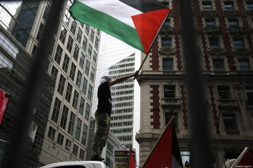 A man waves a Palestinian flag over a vehicle during a protest, organized to mark the 70th anniversary of Nakba, also known as Day of the Catastrophe in 1948, and against the Israeli violence in Gaza on May 18, 2018 at Times Square in New York, United States. [Atılgan Özdil - Anadolu Agency]