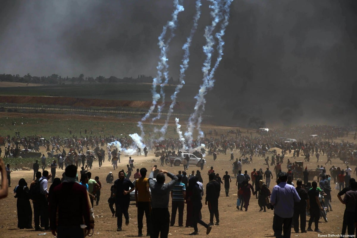 """Palestinian protesters gather during clashes with Israeli security froces in a tent city protest where Palestinians demand the right to return to their homeland, on the occasion of the 70th anniversary of the """"Nakba"""", and against U.S. embassy move to Jerusalem at the Israel-Gaza border, in Beit Lahia, in the northern of Gaza Strip, on 14 May, 2018 [Ramez Habboub/Apaimages]"""