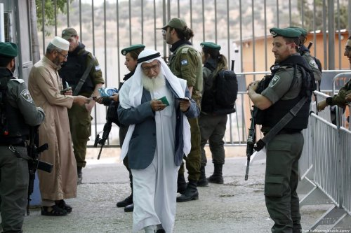 After proving his identity, a Palestinian worshiper walks past Israeli forces to get to Al-Aqsa Mosque on 25 May 2018 [Wisam Hashlamoun/Anadolu Agency]