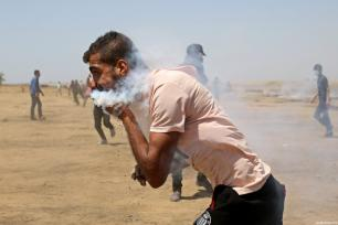 23-year-old Haitham Abu Sabla runs as he holds a teargas canister stuck on his face during a demonstration commemorating the Naksa, along the border with Israel, east of Khan Yunis in the southern Gaza Strip on June 8, 2018 [Ashraf Amra / Anadolu Agency]