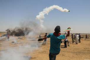 """Palestinian man uses racket to throw gas cannisters back to Israeli forces during the protests called """"commemorating the Naksa"""", along the border fence, east of Khan Yunis in the southern Gaza Strip on June 8, 2018 [Mustafa Hassona / Anadolu Agency]"""
