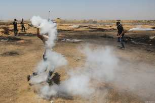 "Palestinian man uses racket to throw gas cannisters back to Israeli forces during the protests called ""commemorating the Naksa"", along the border fence, east of Khan Yunis in the southern Gaza Strip on June 8, 2018 [Mustafa Hassona / Anadolu Agency]"