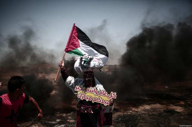 "Palestinian holds a banner reading ""Eid Mubarak"" as they burn tyres in response to Israeli security forces' intervention during the protests called ""commemorating the Naksa"", along the border fence, east of Khan Yunis in the southern Gaza Strip on June 8, 2018 [Mustafa Hassona / Anadolu Agency]"
