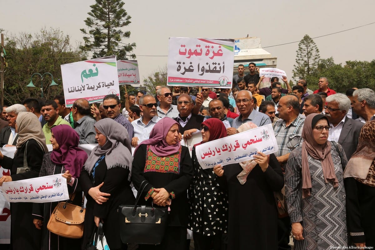 Palestinian Authority employees in the Gaza Strip take part in a protest demanding their salaries in Gaza city on 10 May 2018 [Dawoud Abo Alkas/Apaimages]