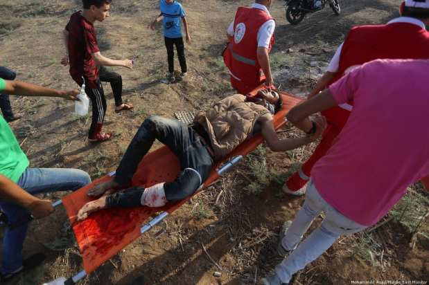 An injured Palestinian is seen after Israeli forces fired tear gas at protesters during the Great March of Return in Gaza on 23 June 2018 [Mohammed Asad/Middle East Monitor]