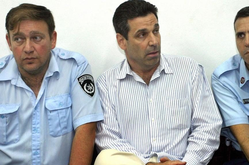 Former Israeli Energy Minister Gonen Segev, seen in police custody in 2004 [Getty]