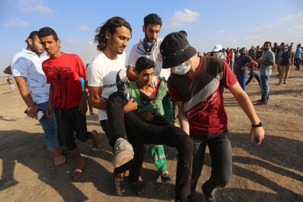 An injured Palestinian is seen taken away as Israeli forces clash with Palestinian protesters at the Gaza and Israel border during the 10th consecutive week of protests, organised as part of the Great March of Return, on 1 June 2018 [Mohammad Asad / Middle East Monitor]