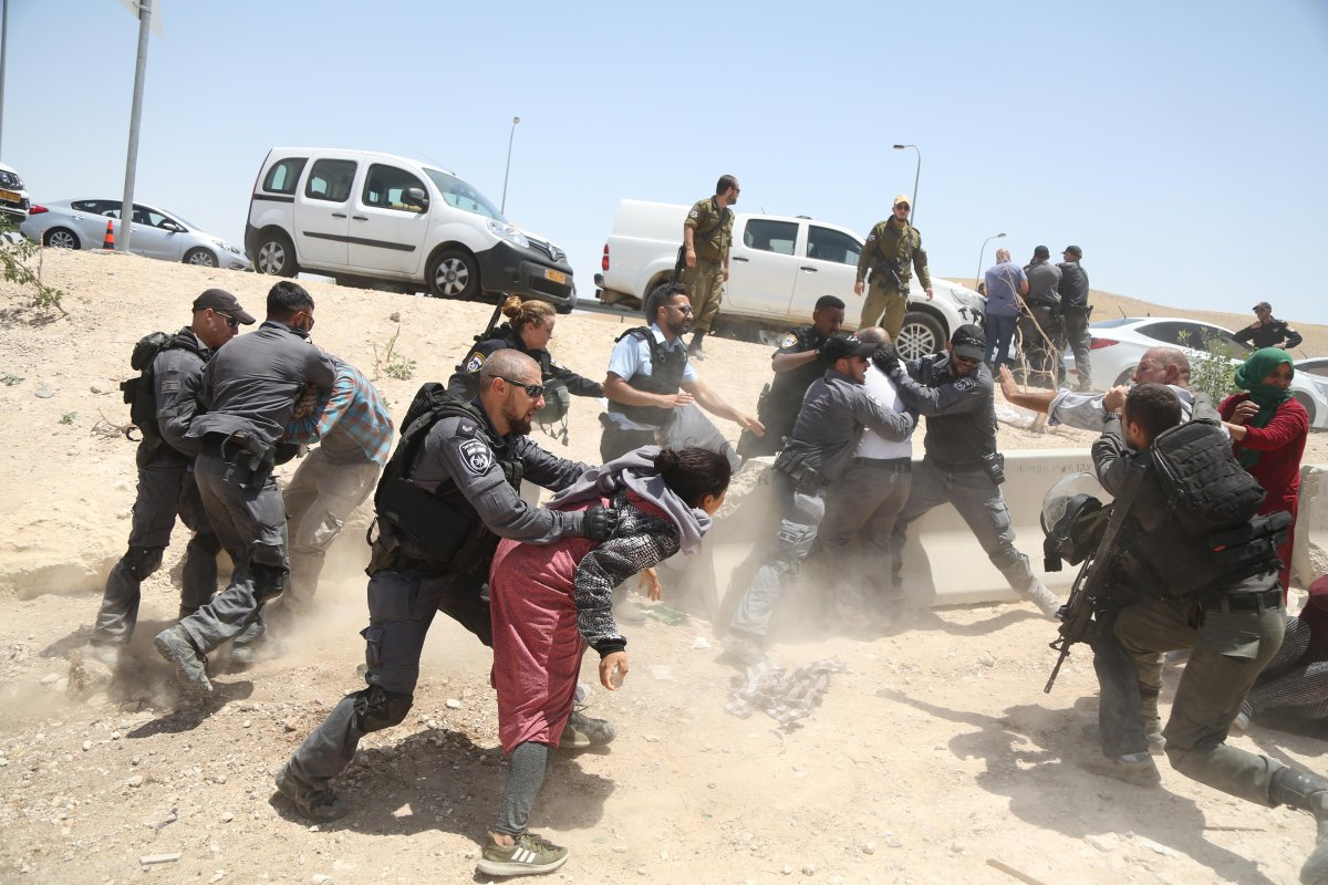 Israeli security forces take a Palestinian into custody as Palestinians try to prevent them to destroy their tents and sheds with bulldozers in Khan al-Ahmar village of eastern Jerusalem on 4 July, 2018 [Issam Rimawi/Anadolu Agency]
