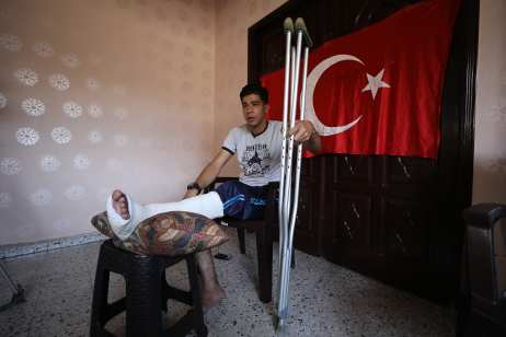"A Palestinian young Emin Selim (20) watches the moments of getting shot as he speaks to press in front of Turkish flag at his home after he was shot by Israeli army while he was waving a Turkish flag during a protest within the ""Great March of Return"" demonstrations near Israel-Gaza border, at Shujaiyya neighbourhood of Gaza City, Gaza on 4 July, 2018 [Mustafa Hassona/Anadolu Agency]"