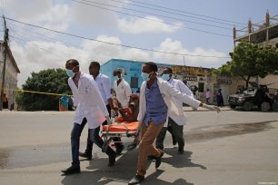 Health staff carry an injured person with a stretcher after a bomb laden car attack by al-Shabab militants in front of Interior Ministry in Mogadishu, Somalia on July 07, 2018 [Sadak Mohamed / Anadolu Agency]