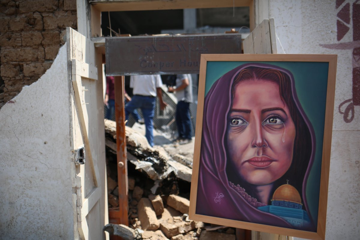 A painting in a frame is seen during an exhibition that held by a group of Palestinian artists, after Israeli forces hit the area with airstrikes at the Art and Craft Village in Gaza City, Gaza on 16 July, 2018 [Hassan Jedi/Anadolu Agency]