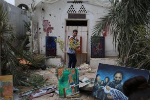 A man takes a look at paintings among wreckage of buildings during an exhibition that held by a group of Palestinian artists, after Israeli forces hit the area with airstrikes at the Art and Craft Village in Gaza City, Gaza on 16 July, 2018 [Hassan Jedi/Anadolu Agency]