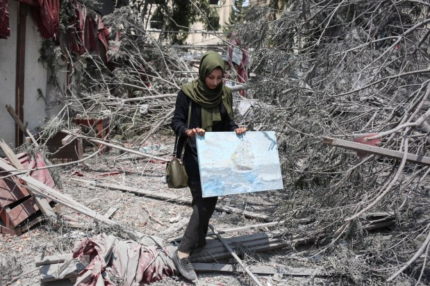 A woman holds a painting among wreckage of buildings during an exhibition that held by a group of Palestinian artists, after Israeli forces hit the area with airstrikes at the Art and Craft Village in Gaza City, Gaza on 16 July, 2018 [Hassan Jedi/Anadolu Agency]