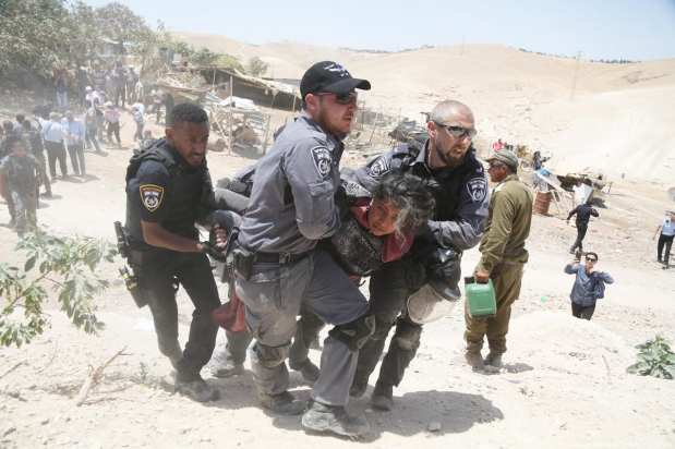 Israeli forces can be seen violently arresting Palestinians who tired to prevent them from demolishing their homes in Khan Al-Ahmar village of eastern Jerusalem on 4 July 2018 [Issam Rimawi/Anadolu Agency]