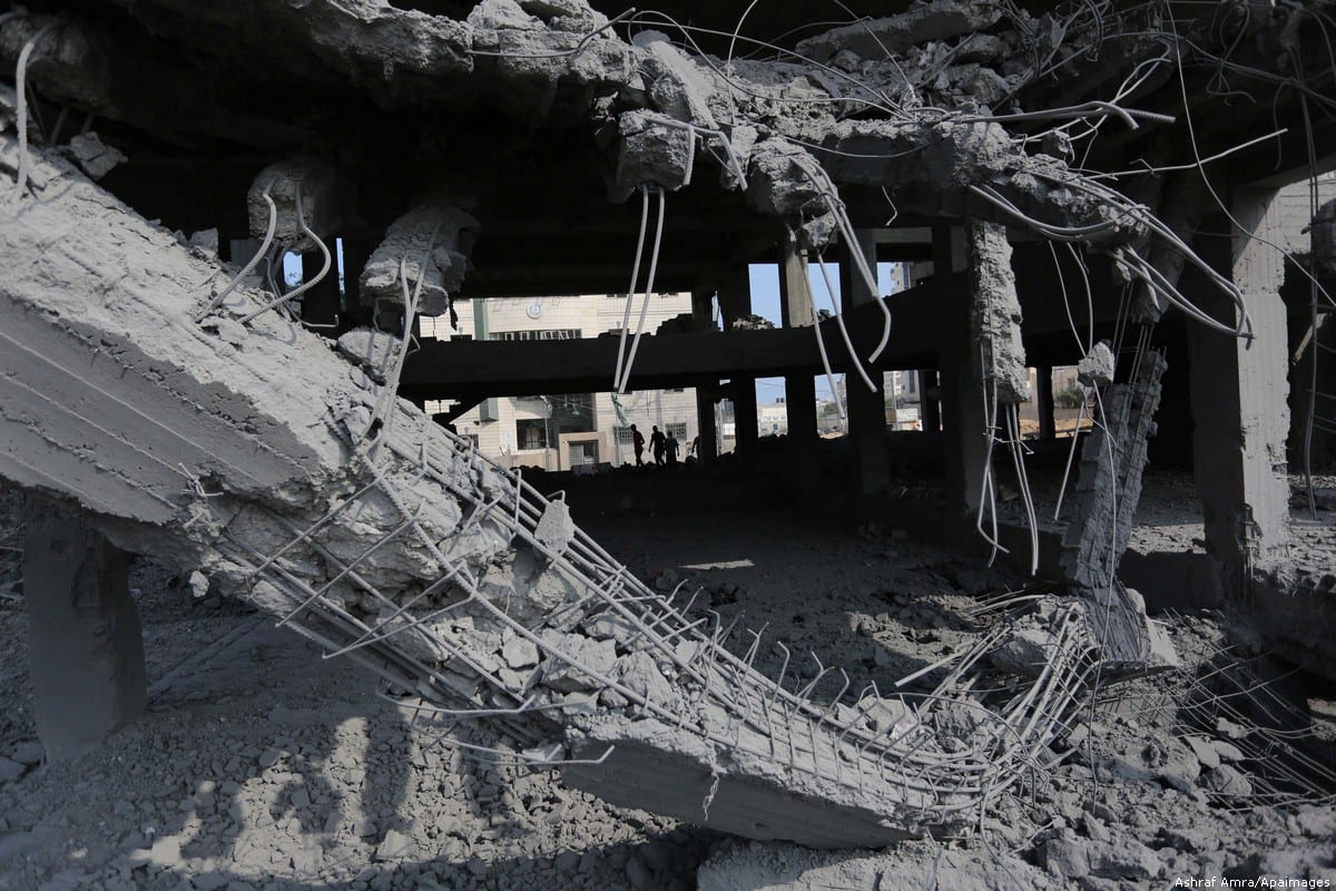 Palestinians inspect the building that was damaged after Israel carried out an air strike in Gaza on 15 July 2018 [Ashraf Amra/Apaimages]
