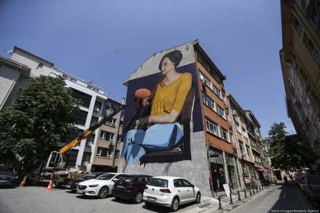 A view of Lonac, an artist from Croatia, working on a mural depicting a woman on the facade of a building as part of the 7th Mural Istanbul Street Art Festival [Veli Gürgah/Anadolu Agency]