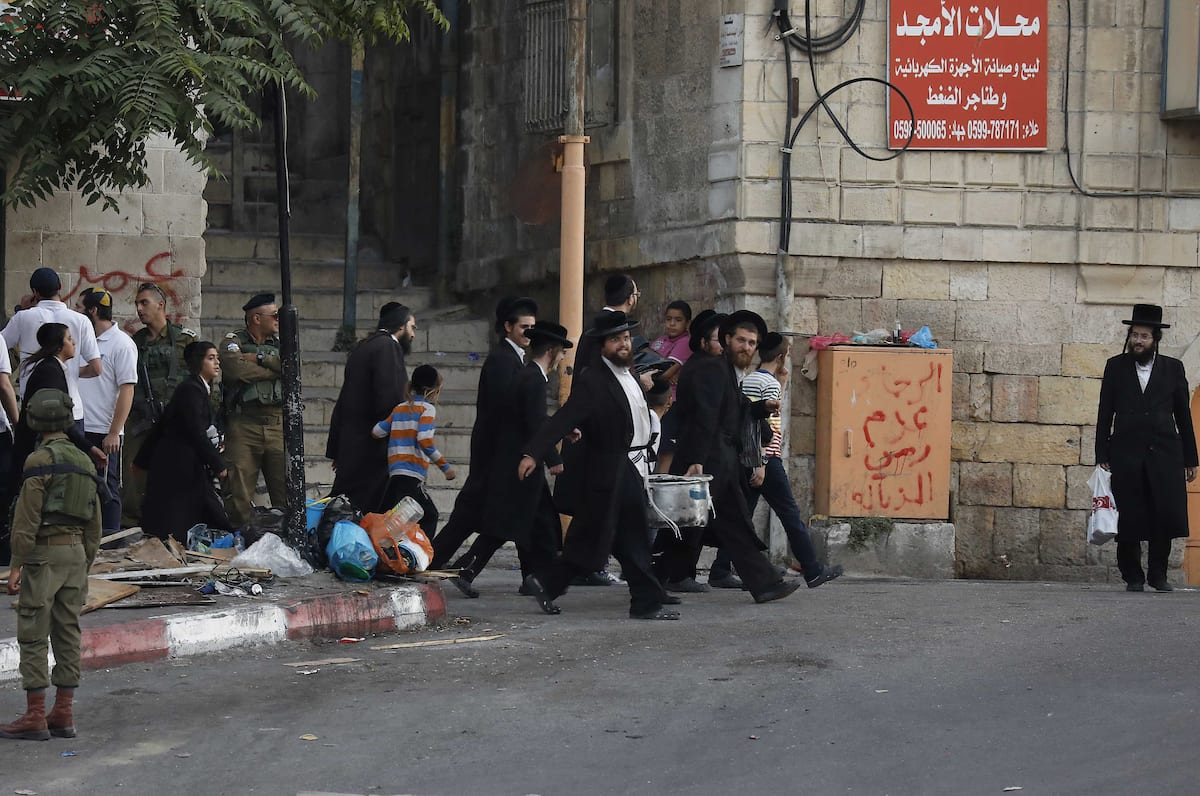 Israeli settlers walk towards the tomb of Atnaeil Ben Kinaz, a Jewish religious site in the divided West Bank town of Hebron on 22 July, 2018 [Wisam Hashlamoun/Apaimages]