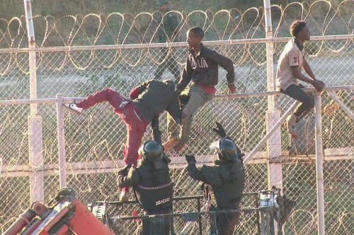 African migrants in this still image from video climb the border from Morocco to Spain's North African enclave of Ceuta, Spain, July 26, 2018. FARO TV/REUTERS TV/via REUTERS