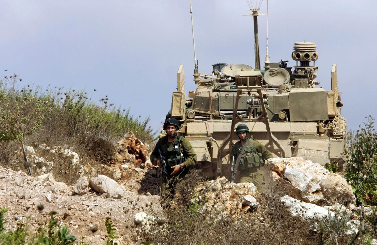 Israeli soldiers patrol around their tanks as they take up positions inside Lebanese territory near the southern Lebanese town of Marwahin, 23 September 2006 [THOMAS COEX/AFP via Getty Images]
