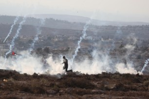 Israeli security forces intervene Palestinians with teargas during a protest held against Jewish occupation over Palestinians' fields in Ras Karkar village of Ramallah, West Bank on 30 August, 2018 [Issam Rimawi/Anadolu Agency]