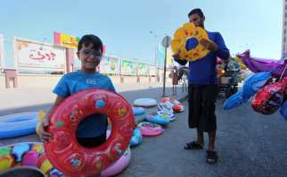 A Palestinian man displays summer games and tires at a street in Gaza city, on 31 July, 2018 [Mahmoud Ajour/Apaimages]
