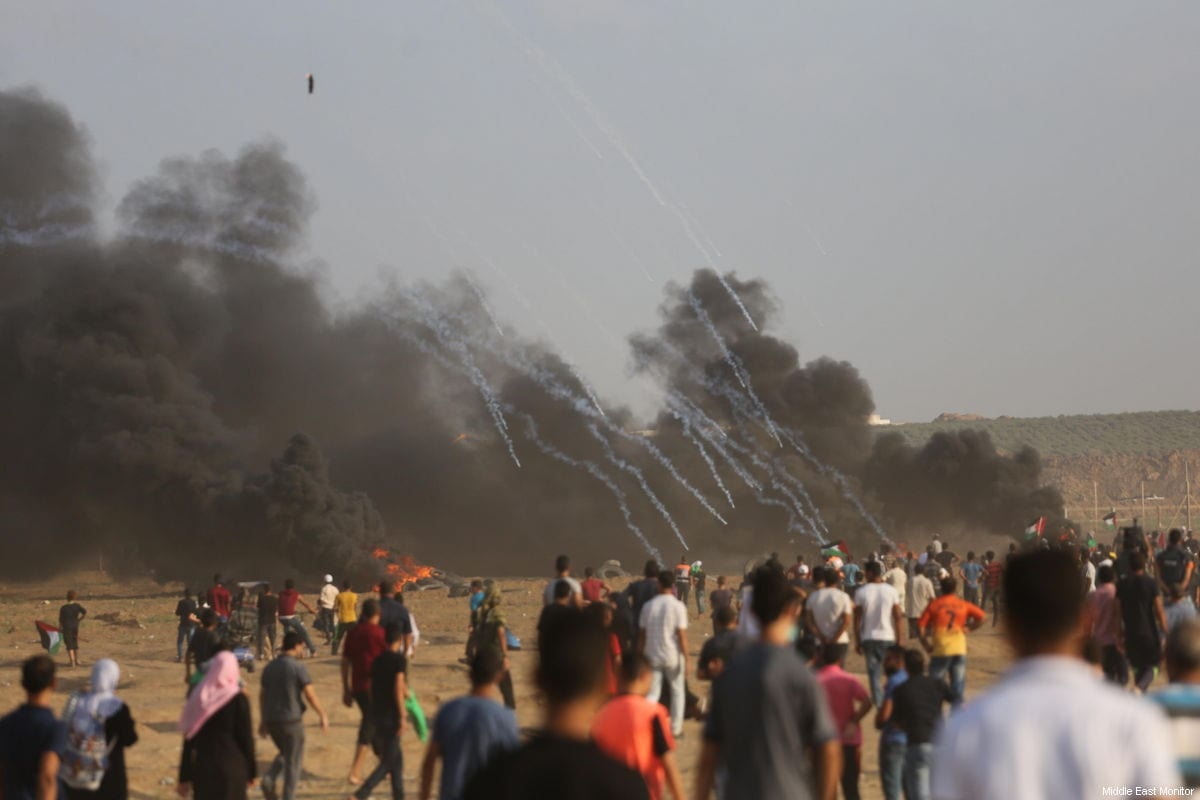 """A Palestinian-launched """"incendiary device"""" [balloon or kite] can be seen in the top-right, as Israeli forces shower Palestinians in a hail of tear gas, at the Gaza-Israel border, gathered as part of the continuing 'Great March of Return' on August 3, 2018 [Mohammad Asad / Middle East Monitor]"""