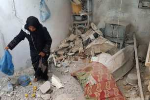 Palestinians clean up the damage done to their home after Israel carried out air strikes in Gaza on 8 August 2018