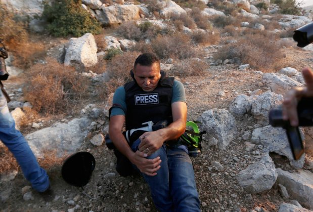 Issam Rimavi, a photojournalist of the Turkey's Anadolu Agency, holds his right knee as he gets injured by the intervention of Israeli forces while covering demonstrations in the village of Ras Karkar near Ramallah, West Bank on September 04, 2018. AFP photographers Abbas Mumini and English Joe Dyke were also hit in the feet after Israeli soldiers opened fire with plastic bullets. ( Shadi Hatem - Anadolu Agency )
