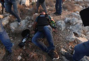 Issam Rimavi, a photojournalist of the Turkey's Anadolu Agency, lies on the floor as he gets injured by the intervention of Israeli forces while covering demonstrations in the village of Ras Karkar near Ramallah, West Bank on September 04, 2018. AFP photographers Abbas Mumini and English Joe Dyke were also hit in the feet after Israeli soldiers opened fire with plastic bullets. ( Shadi Hatem - Anadolu Agency )