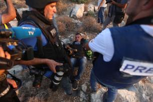 Issam Rimavi (on the floor), a photojournalist of the Turkey's Anadolu Agency, lies on the floor as he gets injured by the intervention of Israeli forces while covering demonstrations in the village of Ras Karkar near Ramallah, West Bank on September 04, 2018. AFP photographers Abbas Mumini and English Joe Dyke were also hit in the feet after Israeli soldiers opened fire with plastic bullets. ( Shadi Hatem - Anadolu Agency )