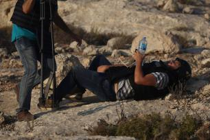 AFP photographer Joe Dyke lies on the floor as he gets injured by the intervention of Israeli forces while covering demonstrations in the village of Ras Karkar near Ramallah, West Bank on 4 September, 2018 [Issam Rimawi/Anadolu Agency]