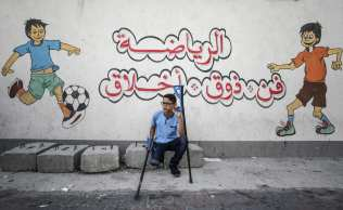 """Palestinian student Mohammed Abu Hussain from Gaza, who lost his leg after being shot by an Israeli sniper during """"Great March of Return"""" demonstrations, sits on a concrete block to rest on his road to school with his crutches as a painting is seen on a wall on the background shows children play in Gaza City, Gaza on 3 September 2018. ( Ali Jadallah - Anadolu Agency )"""