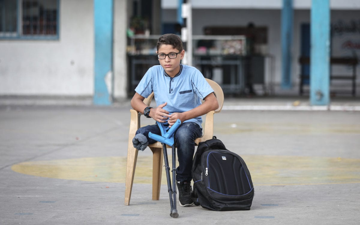 """Palestinian student Mohammed Abu Hussain from Gaza, who lost his leg after being shot by an Israeli sniper during """"Great March of Return"""" demonstrations, sits on a chair holding his crutches at the playground of his school in Gaza City, Gaza on 3 September 2018. [Ali Jadallah - Anadolu Agency]"""
