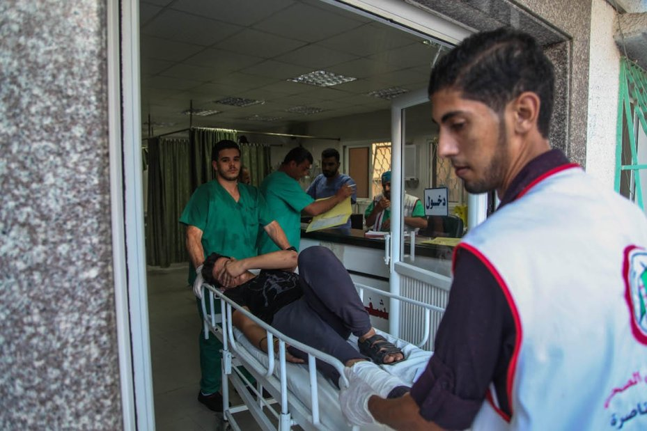A wounded protester receives treatment after Israeli forces attacked them with tear gas canisters during an anti-occupation rally near the Gaza on 18 September 2018 [Ramez Habboub/Anadolu Agency]