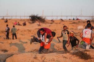 """Palestinians find cover after Israeli intervention with tear gas canisters during the """"Great March of Return"""" demonstration at the Israeli border in eastern Deir Al Balah, Gaza on 27 September, 2018 [Mustafa Hassona/Anadolu Agency]"""