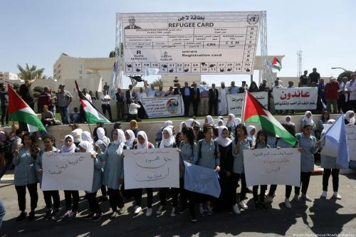 Palestinian refugees hold banners during a protest against the UNWRA's decision on aid cuts and downsizing plans in Bethlehem, West Bank om 26 September 2018 [Wisam Hashlamoun/Anadolu Agency]
