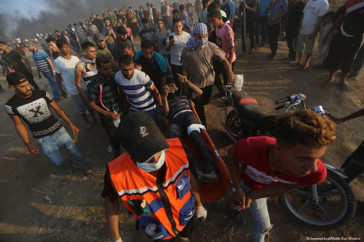 Palestinians protesters carry the injured after Israeli forces carried out tear gas near the Israel - Gaza border [Mohammed Asad/Middle East Monitor]