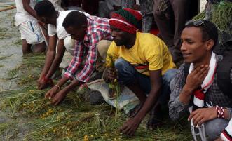 "Oromo people soak grass and pray by the river at the ""Irreecha"" festival (Oromo Thanksgiving) in Addis Ababa, Ethiopia on 30 September, 2018. [Minasse Wondimu Hailu/Anadolu Agency]"