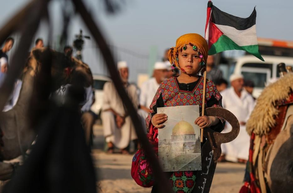 "A girl, in traditional clothes, holds a Palestinian flag and a picture of the Kubbat al-Sahra during the Palestinian and Najaf Bedouin Tribes Festival within the ""Great March of Return"" demonstrations near Gaza border, in Gaza City, Gaza on 2 October 2018 [Mustafa Hassona/Anadolu Agency]"